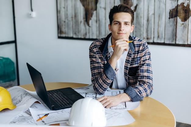 Porträt eines geschäftsmannes im büro, der an seinem schreibtisch arbeitet