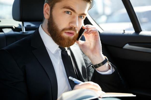 Porträt eines geschäftsmannes mit papieren, die auf smartphone anrufen
