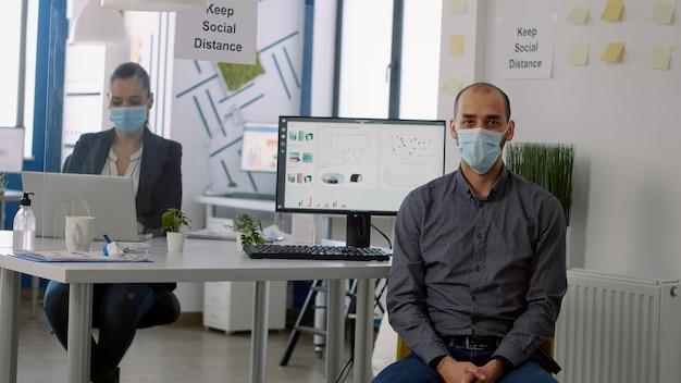 Porträt eines geschäftsmannes mit schützender gesichtsmaske beim sitzen in der unternehmenszentrale des startups. mitarbeiter, die im hintergrund mit laptop-computern arbeiten, halten während der coronavirus-pandemie soziale distanzierung aufrecht
