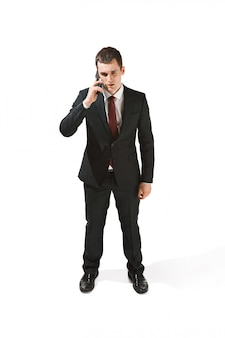 Porträt eines geschäftsmannes mit sehr ernstem gesicht und telefonieren