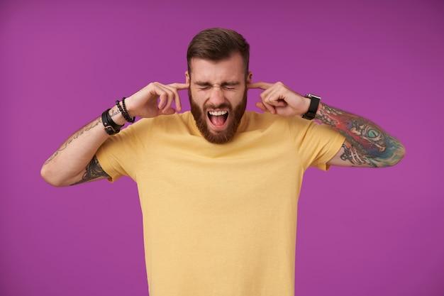 Porträt eines gestressten jungen tätowierten, nicht rasierten mannes, der wegen lauten geräusches seine ohren berührt, die augen geschlossen hält und den mund weit öffnet und sein gesicht runzelt, während er auf lila steht
