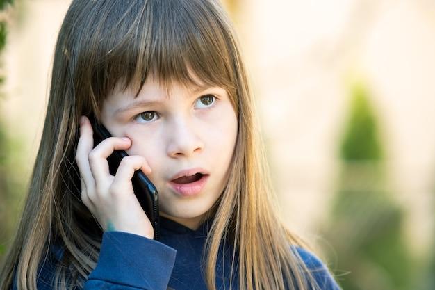 Porträt eines gestressten mädchens mit langen haaren, das am handy spricht. kleines weibliches kind, das mit smartphone kommuniziert. kommunikationskonzept für kinder.