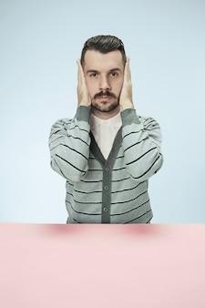 Porträt eines gestressten mannes, der mit geschlossenen augen sitzt und mit händen bedeckt. auf blauer wand isoliert.