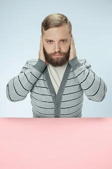 Porträt eines gestressten mannes, der mit geschlossenen augen sitzt und mit händen bedeckt