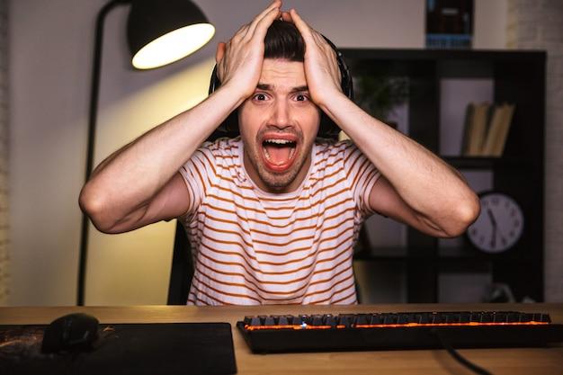Porträt eines gestressten spielertyps, der den kopf packt, während er videospiele am computer spielt und kopfhörer trägt