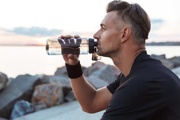Porträt eines gesunden sportlers, der wasser aus einer flasche trinkt
