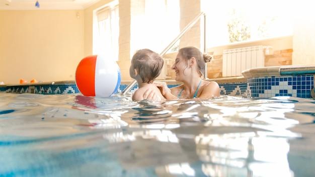 Porträt eines glücklich lachenden kleinkindjungen mit junger mutter, die mit buntem aufblasbarem wasserball im schwimmbad im sommerhotelresort spielt