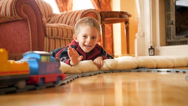 Porträt eines glücklich lächelnden kleinen jungen, der auf dem boden liegt und die hand zum spielzeugzug auf der eisenbahn im wohnzimmer winkt.