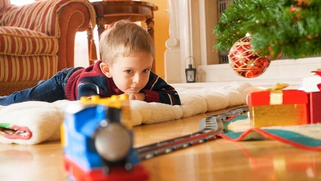 Porträt eines glücklich lächelnden kleinen jungen, der auf holzboden liegt und auf dem zug auf der eisenbahn schaut. kind erhält geschenke und spielzeug an neujahr oder weihnachten