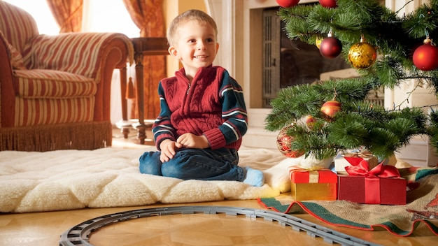 Porträt eines glücklich lächelnden kleinen jungen, der neben weihnachtsbaum und geschenken vom weihnachtsmann im wohnzimmer sitzt