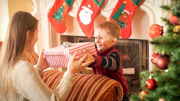 Porträt eines glücklich lächelnden kleinen jungen, der seiner jungen mutter eine große kiste mit weihnachtsgeschenk gibt