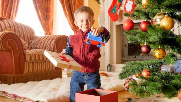 Porträt eines glücklich lächelnden kleinen jungen, der spielzeugeisenbahn aus der weihnachtsgeschenkbox herausnimmt