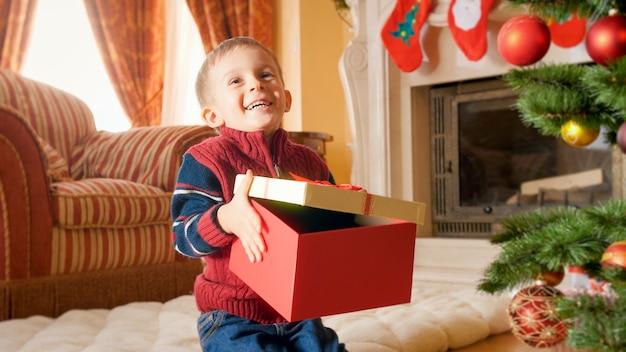 Porträt eines glücklich lächelnden kleinen jungen, der zu weihnachten oder neujahr eine große kiste mit geschenken hält und öffnet