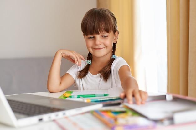 Porträt eines glücklich lächelnden schulkindes, das weißes t-shirt trägt, das am tisch gegen das fenster mit vorhängen vor dem laptop sitzt, positiven ausdruck hat, hausaufgaben macht.