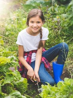 Porträt eines glücklich lächelnden teenager-mädchens, das am sonnigen tag im garten salat pflanzt?