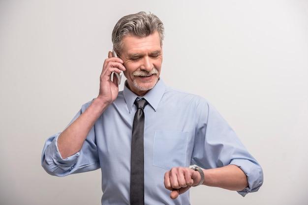 Porträt eines glücklichen älteren mannes, der am telefon spricht.