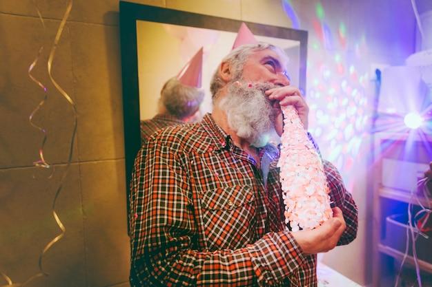 Porträt eines glücklichen älteren mannes, der den alkohol auf geburtstagsfeier genießt