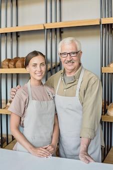 Porträt eines glücklichen älteren mannes, der seine tochter gegen die anzeige umarmt, die sie in der bäckerei zusammenarbeiten