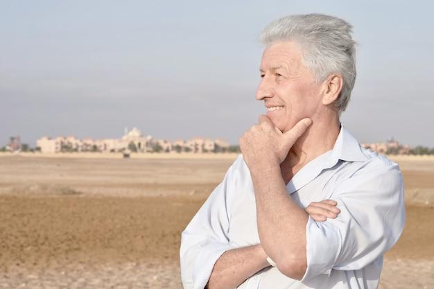 Porträt eines glücklichen älteren mannes in der wüste