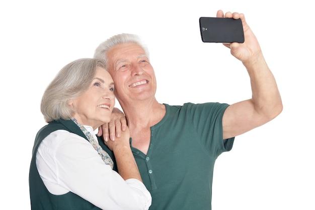 Porträt eines glücklichen älteren paares, das selfie foto auf weißem hintergrund macht