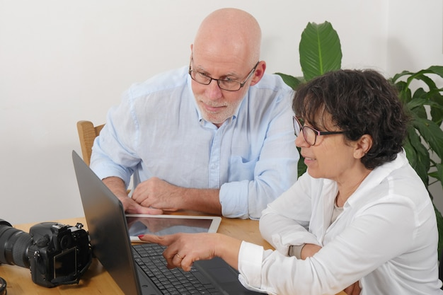 Porträt eines glücklichen älteren paares unter verwendung des laptops