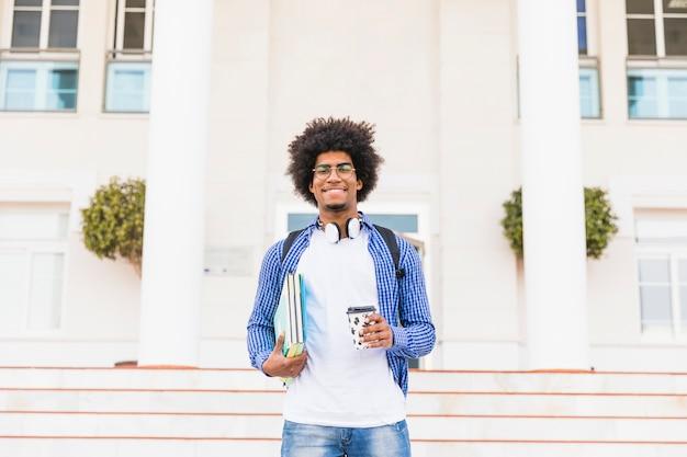 Porträt eines glücklichen afrikanischen jugendlichen männlichen studenten, der die bücher und mitnehmerkaffeetasse stehen vor college hält