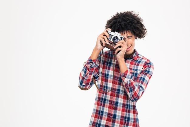 Porträt eines glücklichen afroamerikanischen mannes, der foto auf retro-kamera macht, isoliert auf einer weißen wand