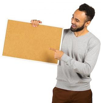 Porträt eines glücklichen afroamerikanischen mannes, der leeres brett lokalisiert auf einem weißen hintergrund hält