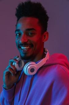 Porträt eines glücklichen afroamerikanischen mannes in einem bunten hoodie, der mit kopfhörern posiert, die über einer violetten wand isoliert sind?