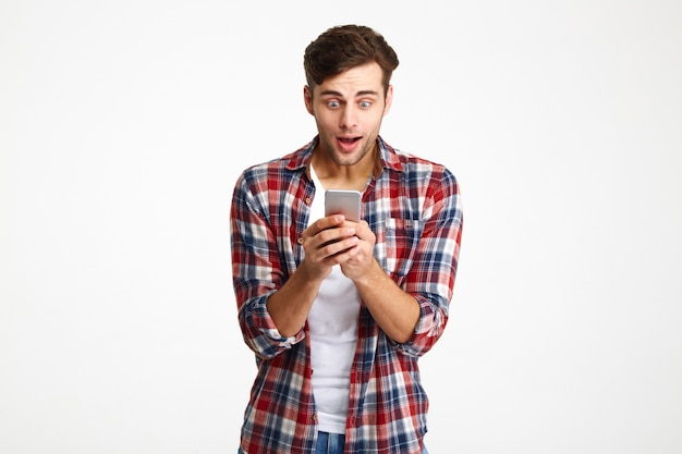Porträt eines glücklichen amüsierten mannes, der handy ansieht
