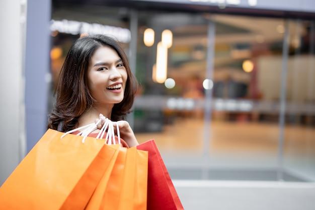 Porträt eines glücklichen asiatischen hübschen mädchens, das einkaufstaschen hält