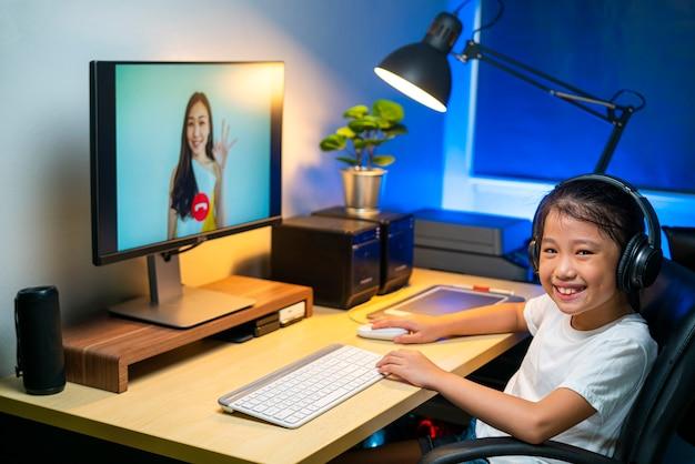 Porträt eines glücklichen asiatischen mädchens, das videokonferenz für das online-lernen mit ihrem lehrer zu hause verwendet.