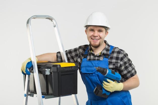 Porträt eines glücklichen baumeisters im weißen helm mit schraubenzieher mit handschuhen und blauen overalls.