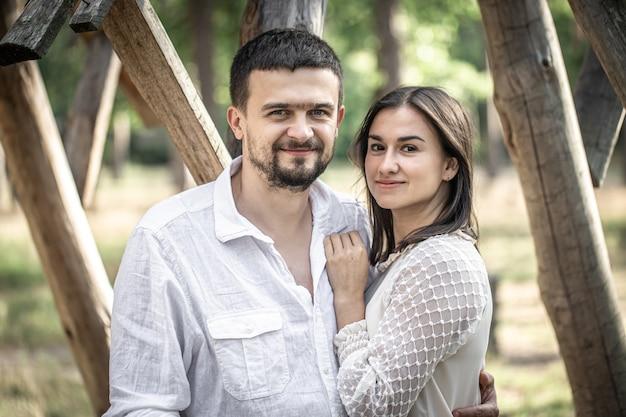 Porträt eines glücklichen ehepaares, des mannes und der frau, die auf einem unscharfen hintergrund im wald umarmen.