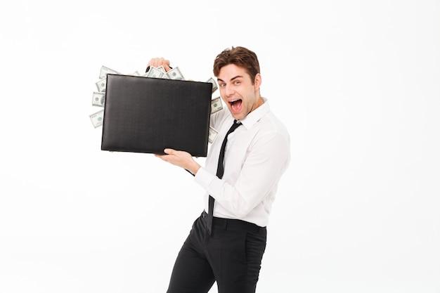 Porträt eines glücklichen erfüllten geschäftsmannes, der aktenkoffer zeigt