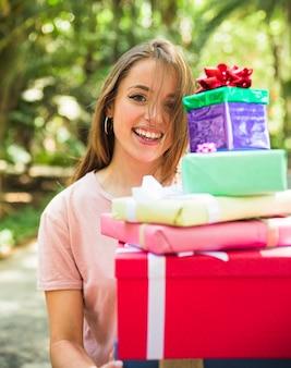 Porträt eines glücklichen frauenholdingstapels geschenke