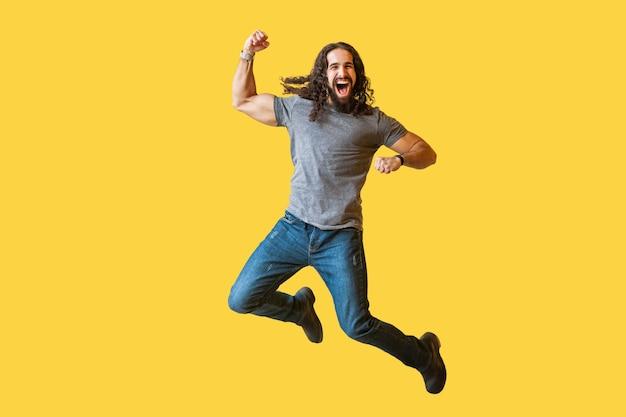 Porträt eines glücklichen, fröhlichen, bärtigen jungen mannes mit langen lockigen haaren in lässigem grauem t-shirt, das springt und seinen sieg mit erstauntem aufgeregtem gesicht feiert. indoor-studioaufnahme auf gelbem hintergrund isoliert.