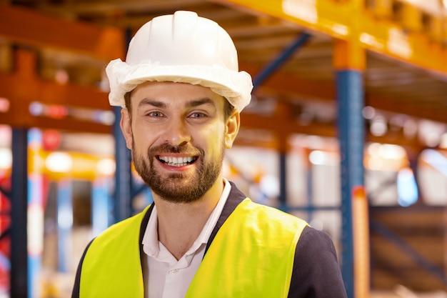 Porträt eines glücklichen fröhlichen mannes, der lächelt, während er eine arbeitsuniform trägt