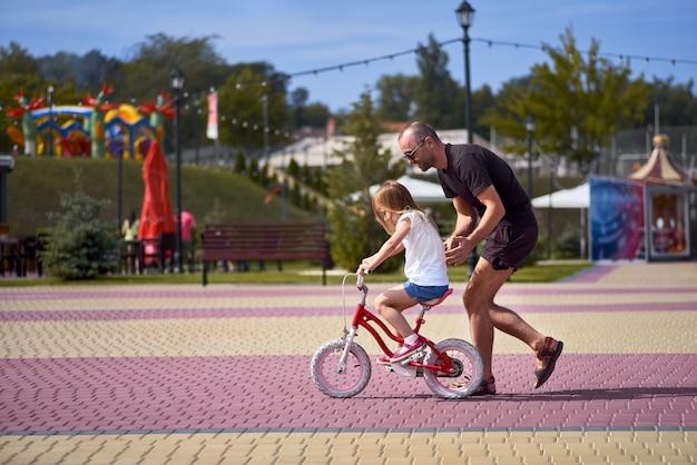 Porträt eines glücklichen fürsorglichen vaters, der seine kleine hübsche tochter unterrichtet, die fahrrad in einem grünen park fährt und in voller länge lächelt