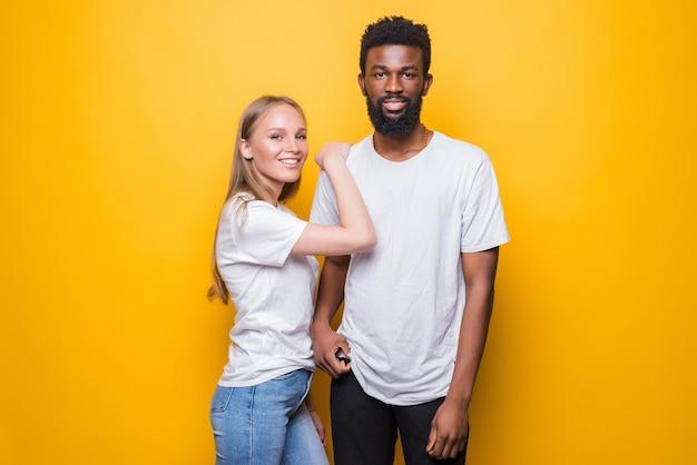 Porträt eines glücklichen gemischtrassigen paares, das sich zusammen über der gelben wand im studio umarmt und aufwirft