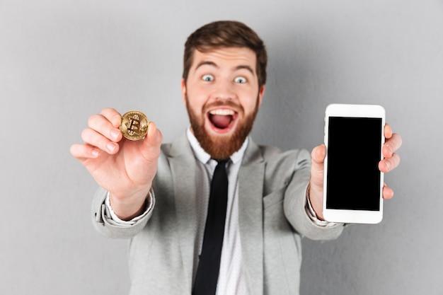 Porträt eines glücklichen geschäftsmannes, der bitcoin hält