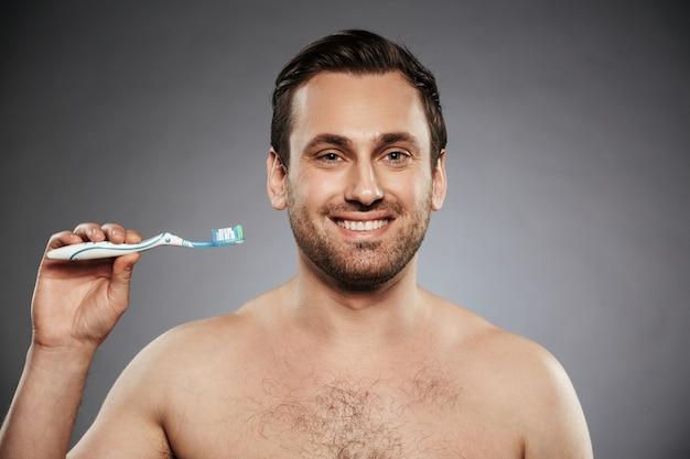 Porträt eines glücklichen hemdlosen mannes, der zahnbürste hält