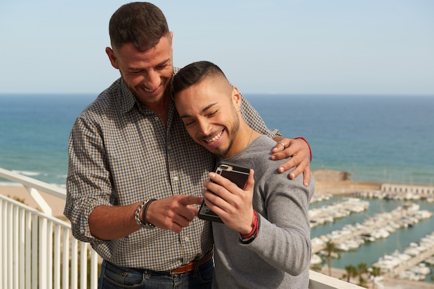 Porträt eines glücklichen homosexuellen paares, das draußen ihren handy überprüft