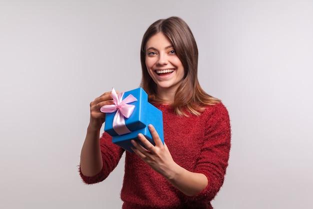 Porträt eines glücklichen hübschen mädchens im pullover, das geschenkbox öffnet und die kamera zufrieden lächelnd anschaut
