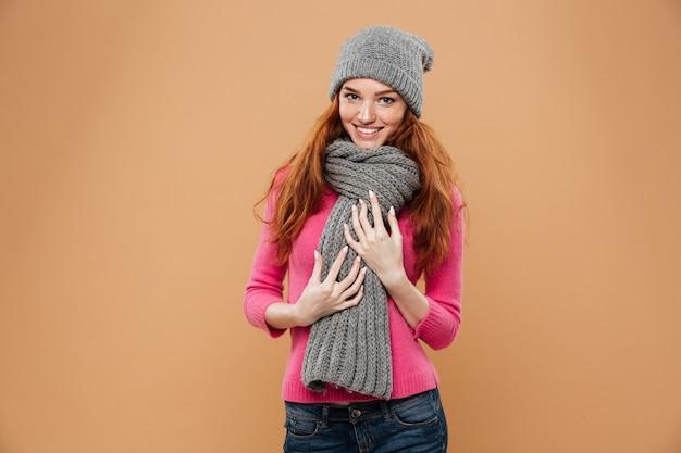 Porträt eines glücklichen hübschen rothaarigemädchens kleidete im winterhut an