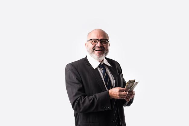 Porträt eines glücklichen indischen asiatischen leitenden geschäftsmannes, der indische banknoten von fünfhundert nennwerten hält
