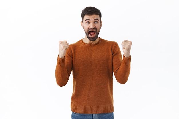 Porträt eines glücklichen, jubelnden bärtigen mannes, der gewinnt, erfolg feiert, ziel und faustpumpe erreicht, ja oder hurra schreit, unterstützend, über den sieg singen, weiße wand stehen