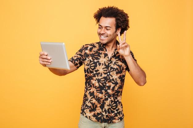 Porträt eines glücklichen jungen afrikanischen mannes, der pc-tablette hält