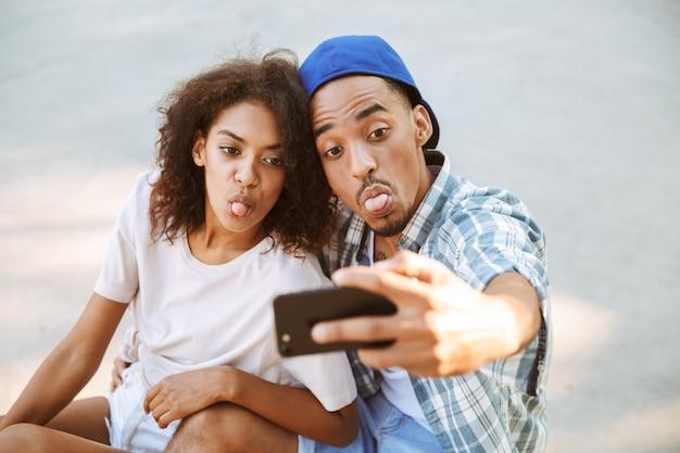 Porträt eines glücklichen jungen afrikanischen paares, das ein selfie nimmt
