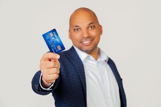 Porträt eines glücklichen jungen afroamerikanischen geschäftsmannes, der eine kreditkarte mit einem glücklichen gesicht hält, steht und lächelt mit einem selbstbewussten lächeln, das zähne zeigt.
